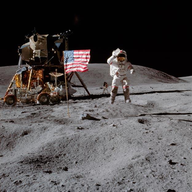 John Young saluda a la cámara con la bandera de EEUU izada