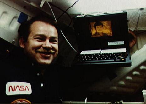 John Creighton posando junto al GRid Compass 1101 en una misión del transbordador espacial Discovery en 1985